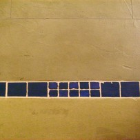 Lehmboden dunkel in Kombination mit blauen Mosaiken
